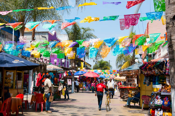 People Shop Beneath Hanging Flags in Tijuana, Mexico stock photo