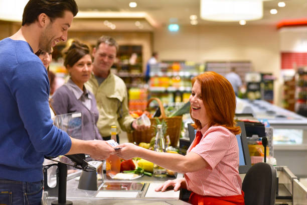 people shopping at the supermarket - paying at the checkout with a friendly cashier - сейфы и хранилища стоковые фото и изображения