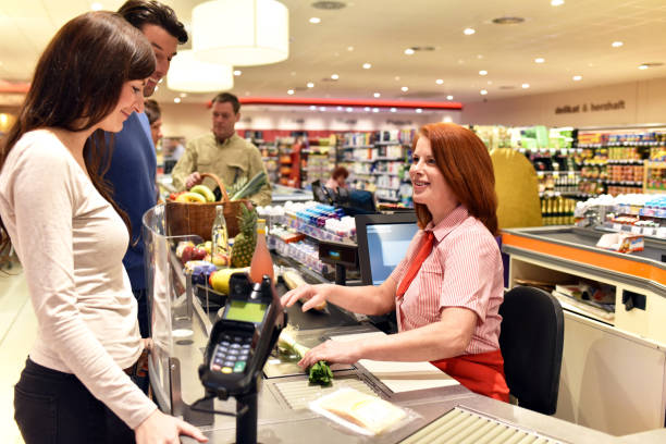 people shopping at the supermarket - paying at the checkout with a friendly cashier stock photo