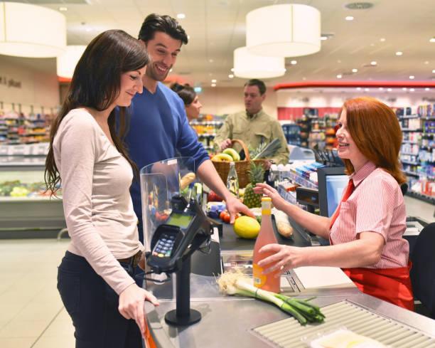 mensen winkelen voor de menselijke voeding in de supermarkt - verkoopster stockfoto's en -beelden