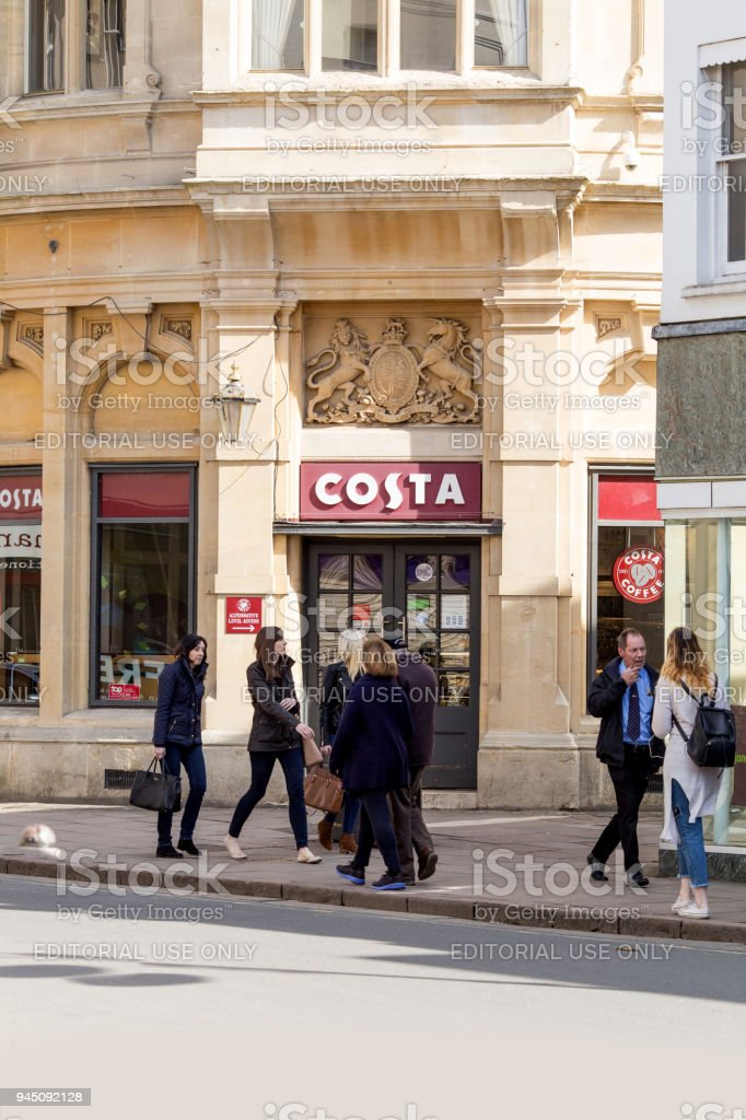 People shopping in Cheltenham town centre, passing the retail coffee outlet - Costa Coffee stock photo