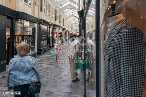 People walking and shopping in the Burlington Arcade, London, England. A man is looking at a shop window.  The Burlington Arcade is Britain's first and longest shopping arcade that opened in 1819