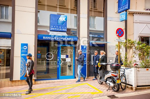 Biarritz, France - May 04, 2019: People sightseeing and shopping in Biarritz city center, France. Banque Populaire with ATM outside and motorcycle parked