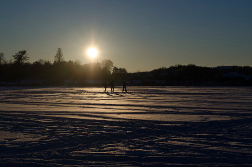 people silhouette  frozen lake snow sunset evening