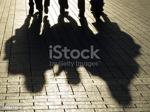 Crowd walking down on sidewalk, concept of strangers, crime, society, urbanisation, city life