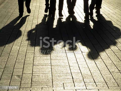 Crowd walking down on sidewalk, concept of strangers, crime, society, street gang