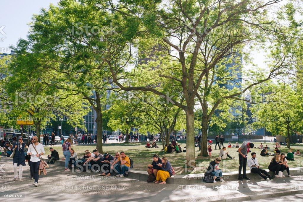 人們坐在波茨坦地方的樹下休息。 - 免版稅人圖庫照片