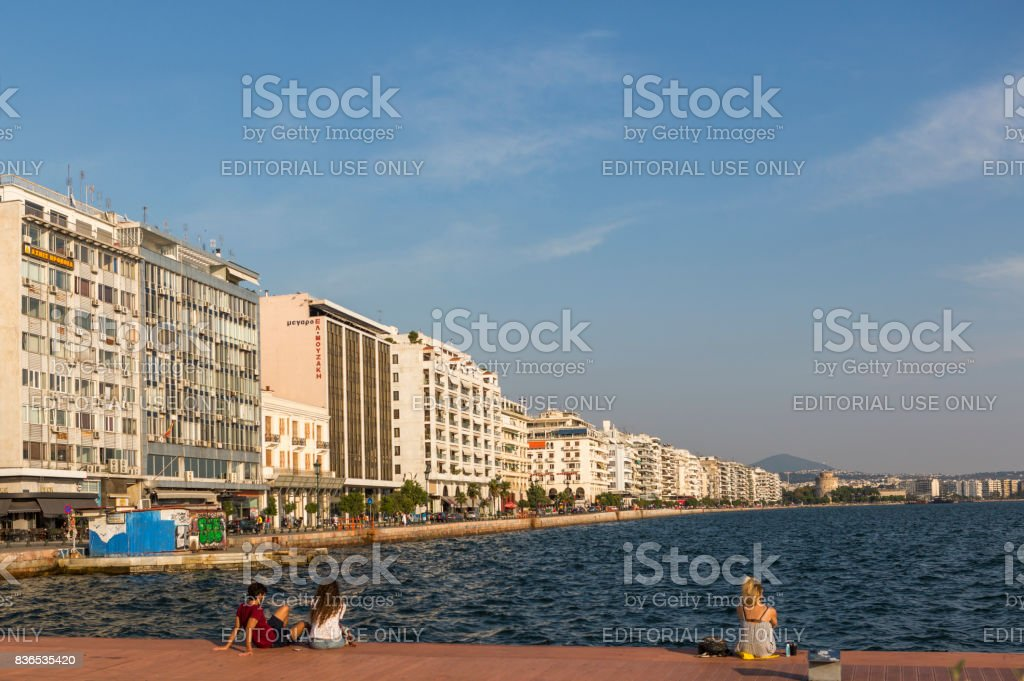 People sit and watch coast of historical city with traditional buildings at Thessaloniki greece stock photo