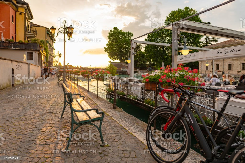 People sit at cafe and walk the quay in Peschiera del Garda on Lake Garda, Italy stock photo