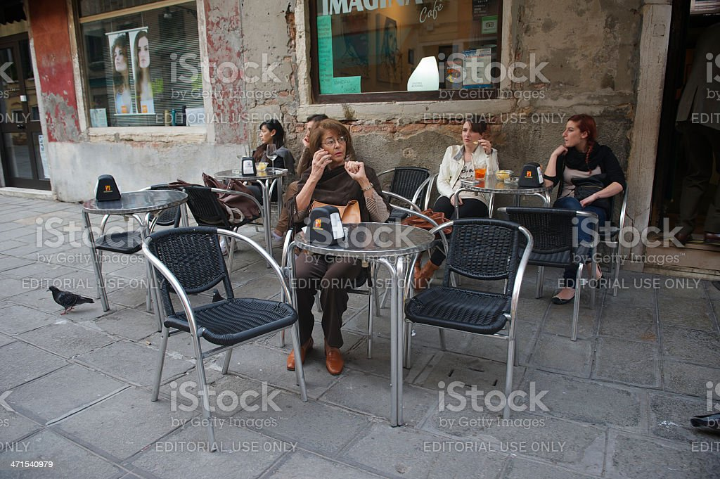 People Sit at Sidewalk Cafe in Venice Italy stock photo