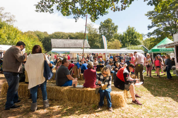 People sit eating on hay at the Food Festival in St Fagans St Fagans, United Kingdom -  July 14, 2017: People sit eating on hay at the Food Festival in St Fagans, Cardiff, Wales food festival stock pictures, royalty-free photos & images