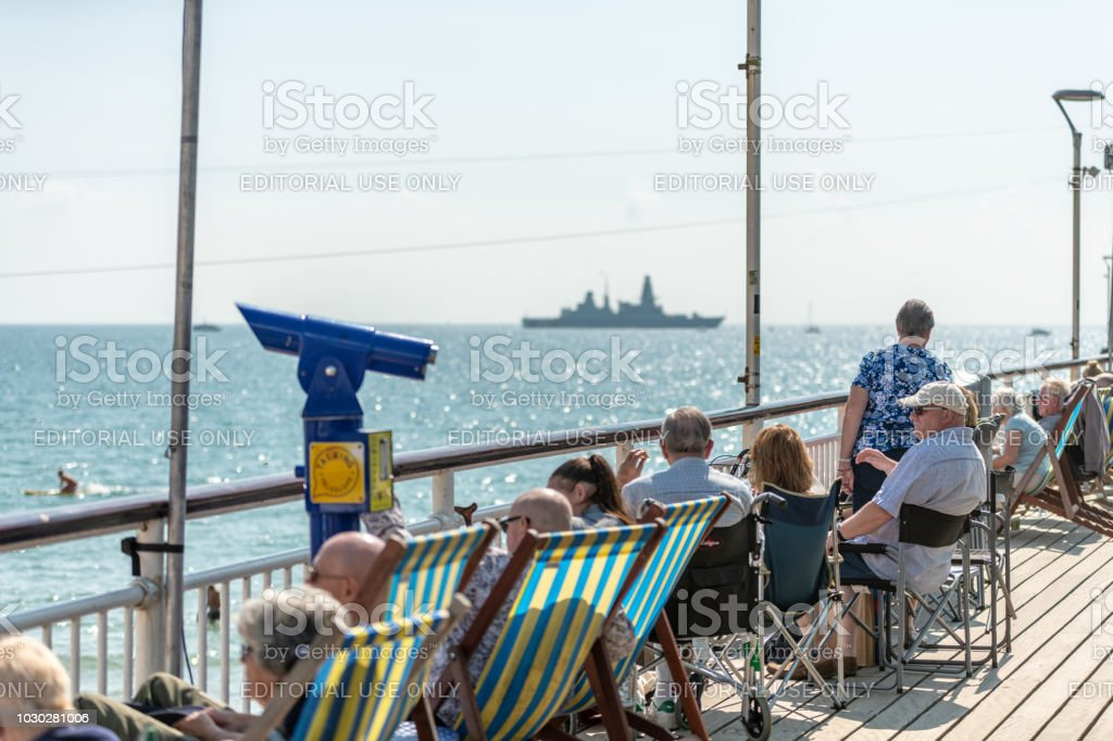 People sit in deckchairs on the pier looking out to sea stock photo