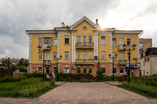 Krasnoyarsk, Krasnoyarsk Region, RF - July 19, 2021: People sit on a bench near a residential building, buildings from Stalin's times with stucco molding from Soviet stars on a cloudy summer day.
