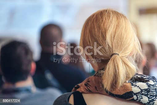 609903512 istock photo People sitting at a big conference hall during video-presentation 530417224