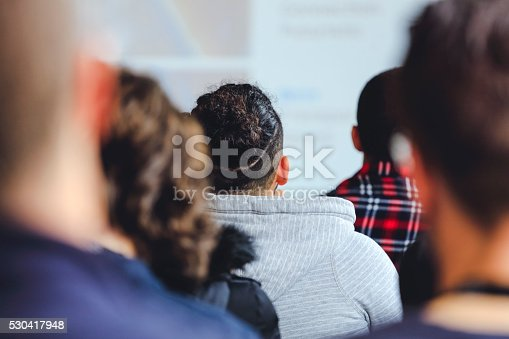 526272636istockphoto People sitting at a big conference hall during video-presentation 530417948
