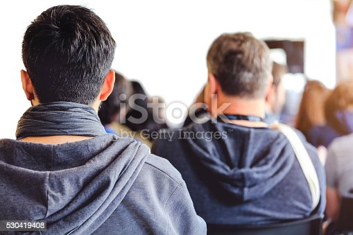 609903512 istock photo People sitting at a big conference hall during video-presentation 530419408