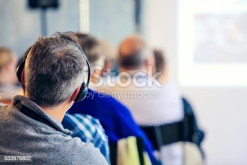 609903512 istock photo People sitting at a big conference hall during video-presentation 533976802
