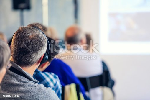 609903512 istock photo People sitting at a big conference hall during video-presentation 533977026