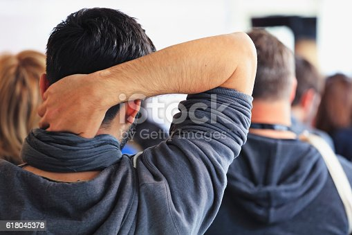 609903512 istock photo People sitting at a big conference hall during video-presentation 618045378