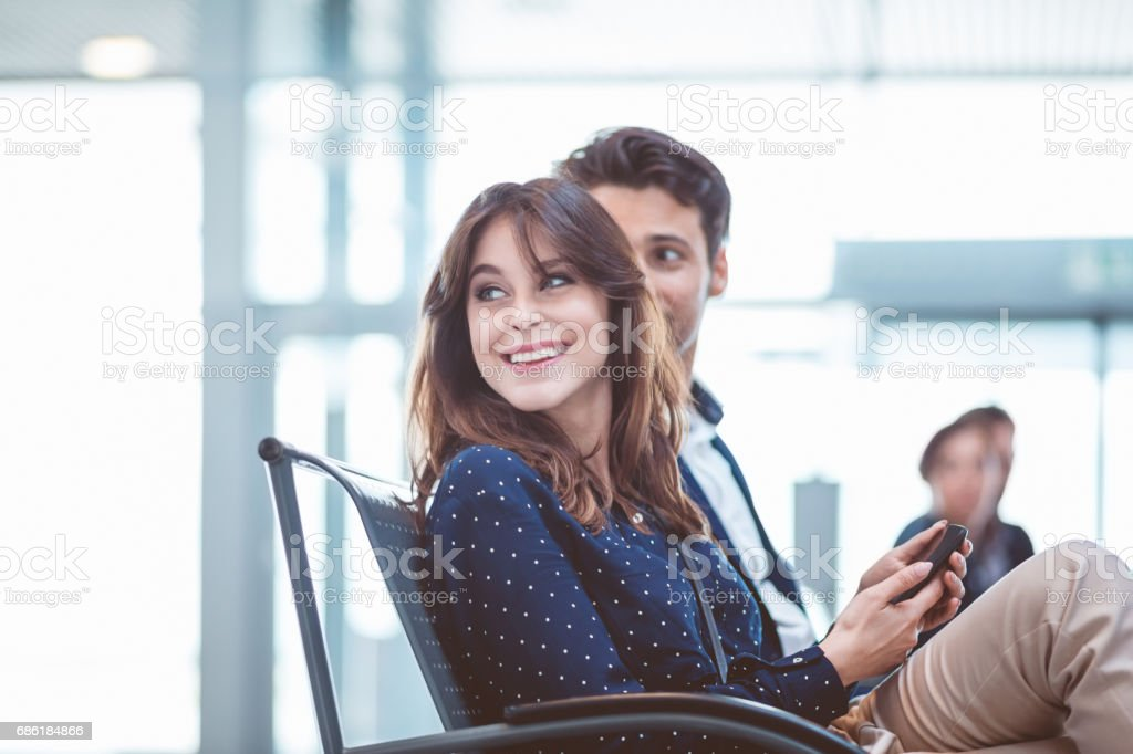 People sitting at airport departure area. stock photo