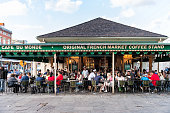 New Orleans, USA - April 22, 2018: People sitting at tables at iconic Cafe Du Monde restaurant sign eating beignet powdered sugar donuts and chicory coffee