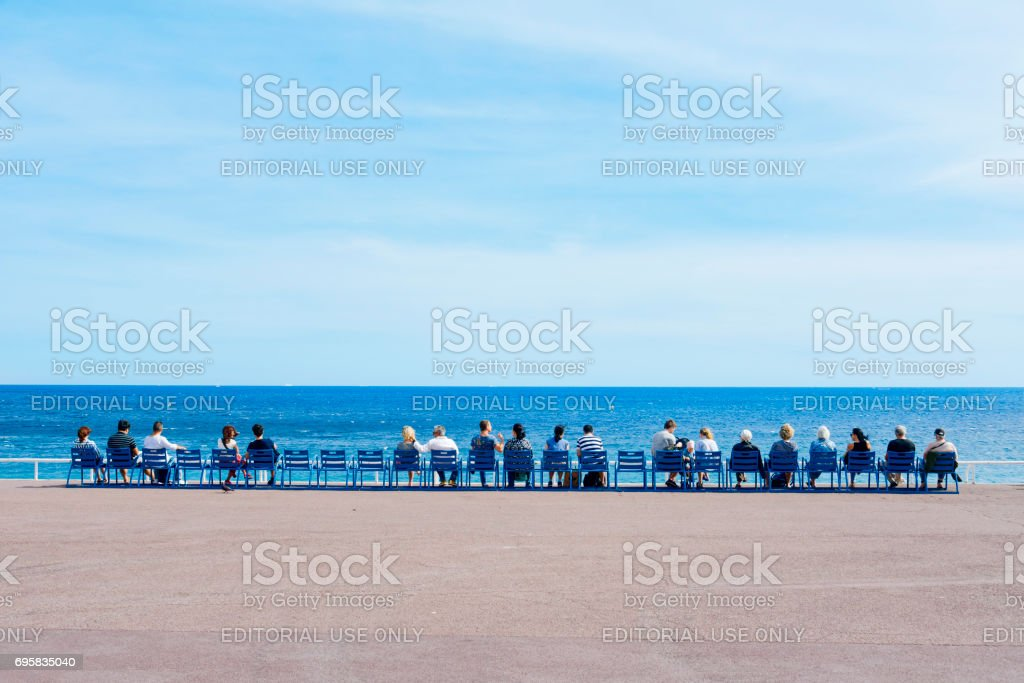 people sitting at the Promenade des Anglais in Nice, France stock photo