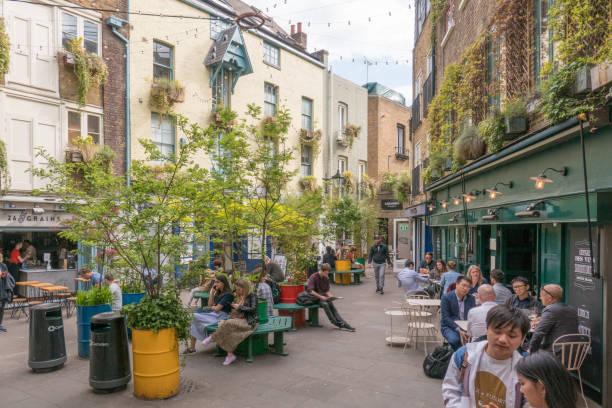 menschen sitzen, trinken, in neals hof, london, england - hofladen stock-fotos und bilder