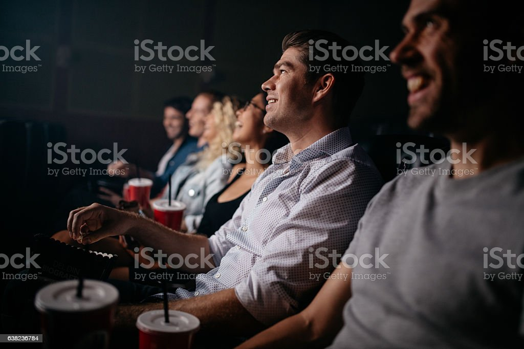 People sitting in cinema hall watching movie stock photo