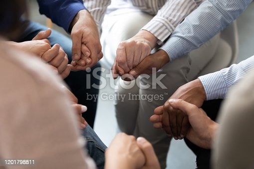 847516586 istock photo People sitting in circle holding hands at group therapy session 1201798811