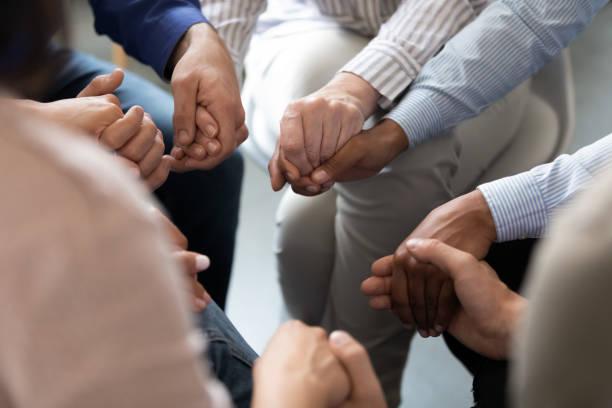 personer som sitter i cirkel håller händerna på gruppterapi session - emotionellt stöd bildbanksfoton och bilder