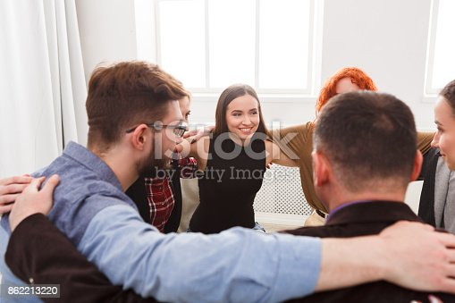 istock People sitting in circle, hugging each other 862213220