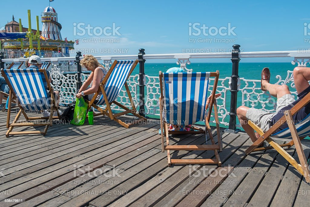 People sitting in deck chair s on the pier stock photo