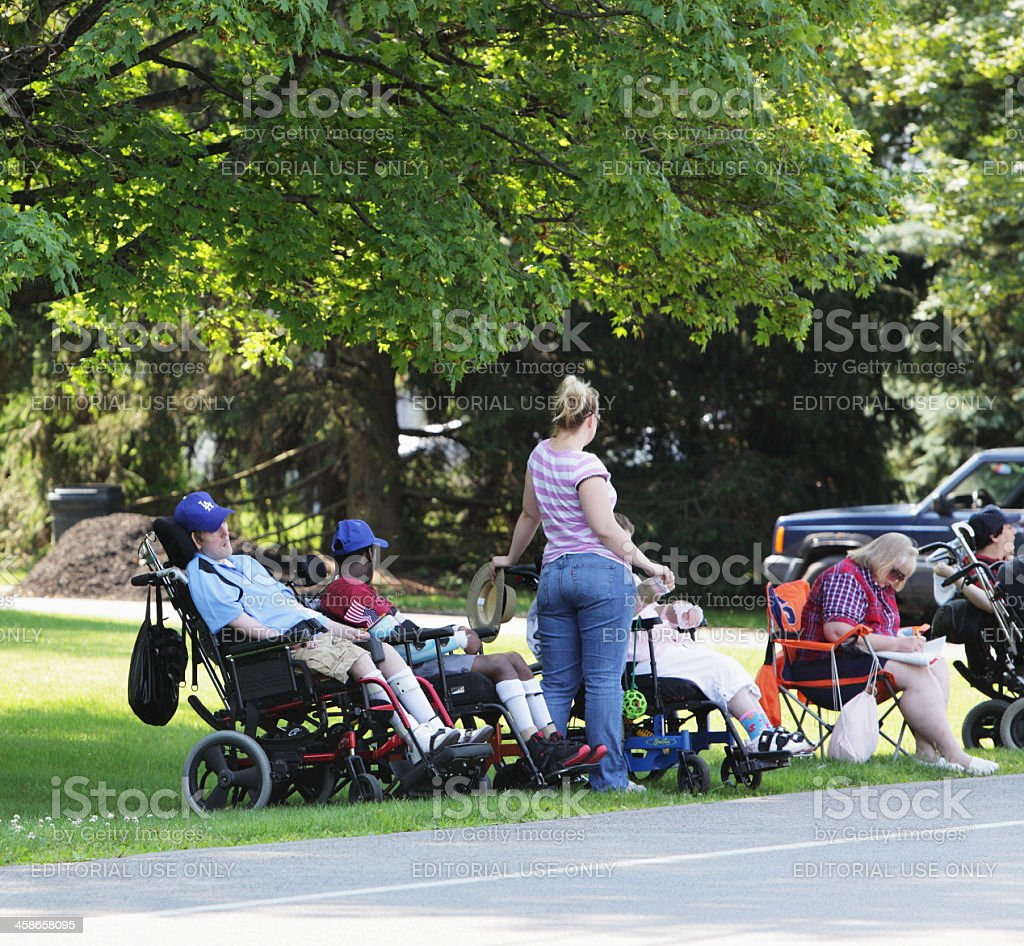 People Sitting in Wheelchairs Waiting for July 4th Parade stock photo