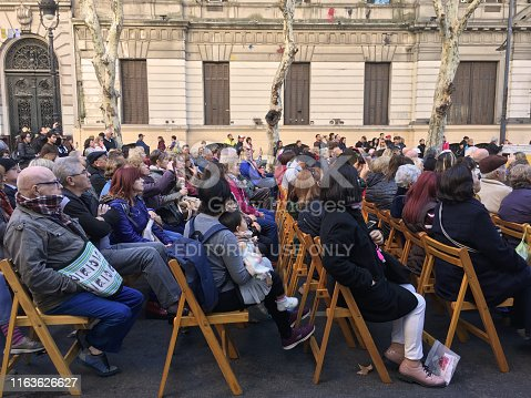 Buenos Aires, Argentina - June 9, 2019: Group of people sitting on chairs placed in the street for an event organized by the city government. Almost every week there are performances in the street where people can go and watch for free