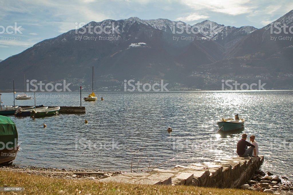People sitting near the lake stock photo