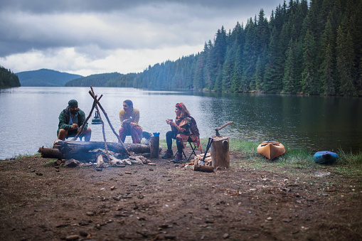 Group of friends are having fun and drinking tea at the nature while they are at a camping vacation