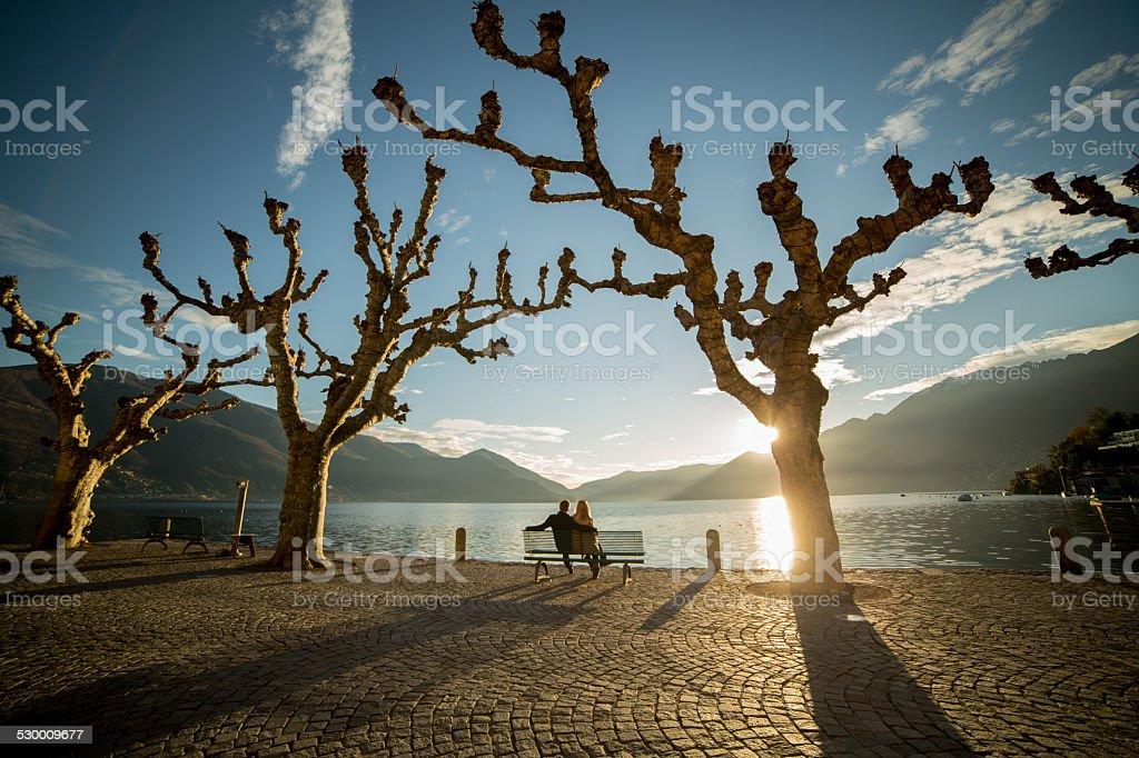 People sitting on bench near lakeshore at sunset-Winter stock photo