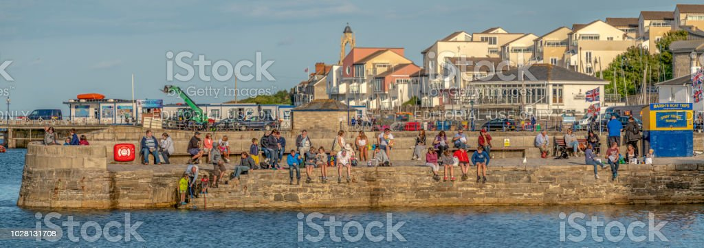 People sitting on the quayside in Swanage, Dorset stock photo