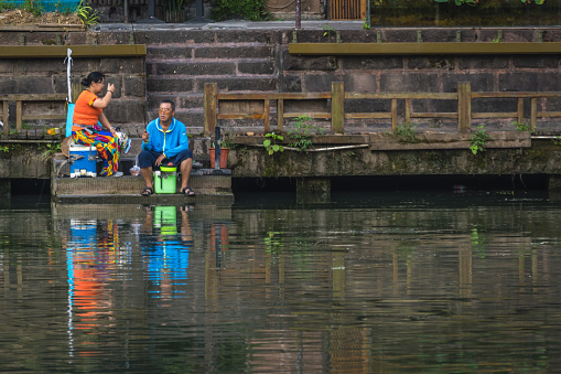 People sitting on the river shore in Fenghuang Old Town
