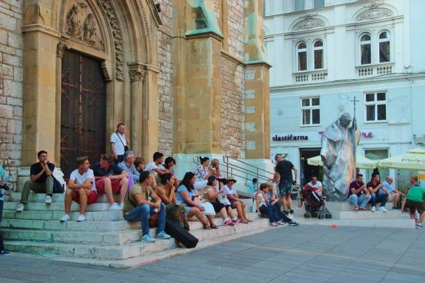 people sitting on the stairs in front of the jesus' sacred heart cathedral in the old town of sarajevo. bosnia and herzegovina. - jesus and heart zdjęcia i obrazy z banku zdjęć