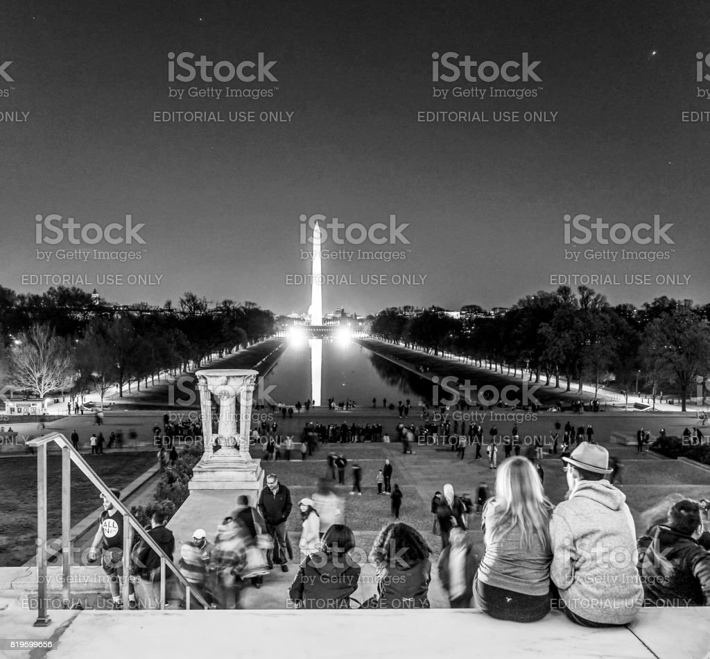 People sitting on the steps of Lincoln Memorial in Washington and view over reflecting pool - WASHINGTON DC - COLUMBIA - APRIL 9, 2017 stock photo