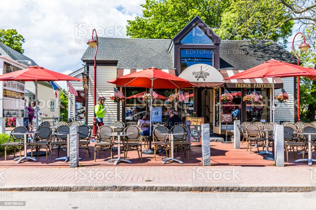 People sitting outside in French restaurant in downtown village during summer day stock photo