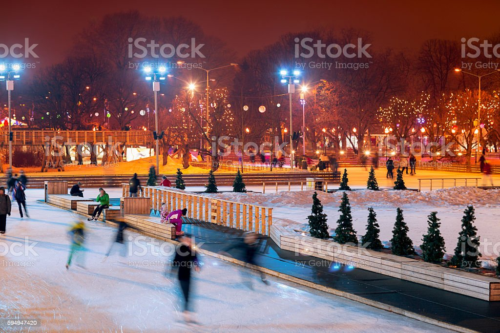 People skate in the evening in the Park in winter. stock photo