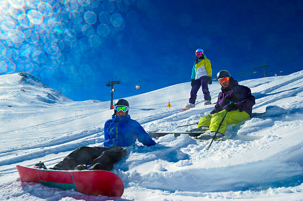 People skiing and snowboarding in powder snow stock photo
