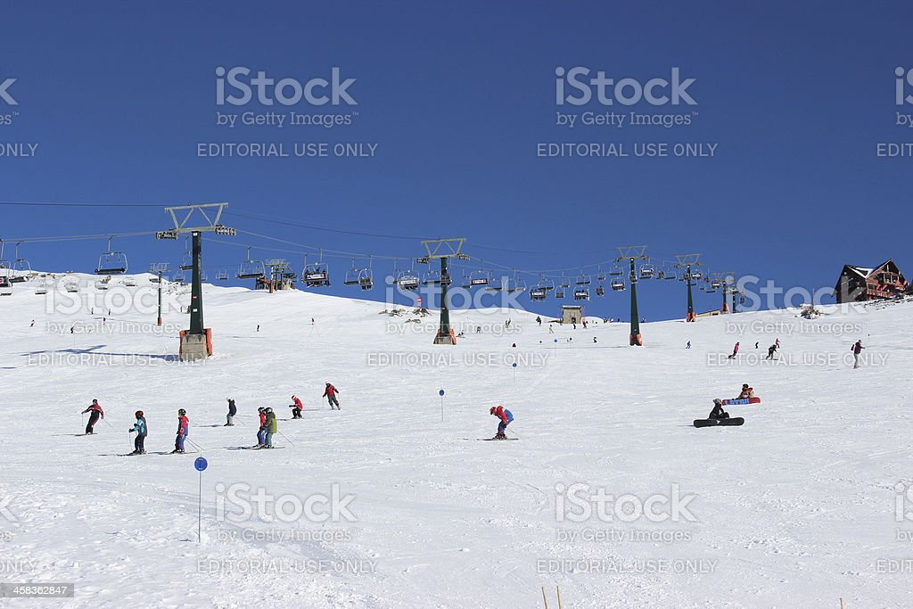 People skiing CERRO CATEDRAL - Lynch Refuge at backgrounf stock photo