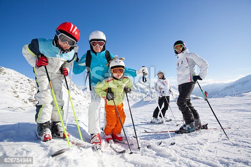 children and adults in skiing clothes with helmets and skis on ski slope