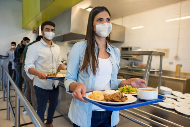 people social distancing and wearing facemasks while having lunch at a buffet - covid restaurant imagens e fotografias de stock