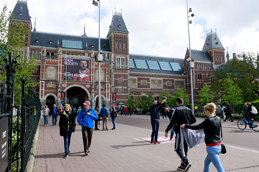 Amsterdam, Netherlands - March 6, 2021: People standing in front of the Rijksmuseum. Due to the rising number of COVID-19 infections, the Netherlands has been in lockdown since 15 December 2020.