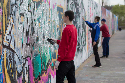 People spraying graffiti on wall in Berlin Mauerpark