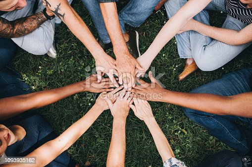 istock People stacking hands together in the park 1093935162